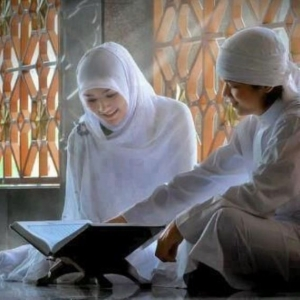 Asian Muslim couple reading Quran