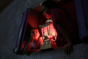 Egyptian children hold a traditional Ramadan lantern placed in a windowsill