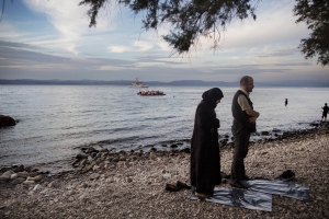 Syrian man and wife pray on Greek beach