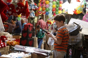 Child inspects toy gun in a souk ahead of Eid al-Fitr celebrations in Damascus