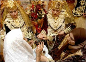 Preparing for a wedding in Algeria. Brides adorned with golden headdresses
