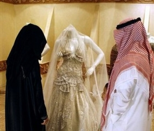 A Saudi couple prepare for their wedding. Admiring a bridal outfit