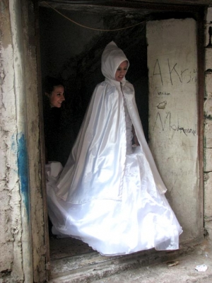 Palestinian bride steps out of her home in traditional bridal dress
