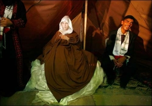 Palestinian groom and bride celebrate their wedding in a tent, Gaza