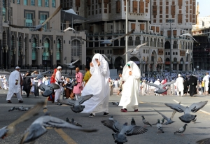 Pigeons fly over Muslim pilgrims near the Grand Mosque in the holy city of Mecca