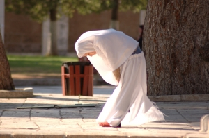 Malay woman praying in a sidewalk