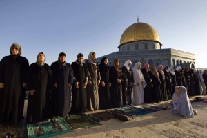 Palestinian women prepare for prayer in front of the Dome of the Rock, Jerusalem