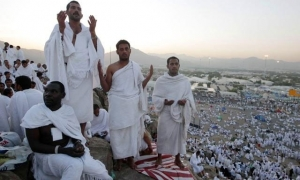 Muslim men, black and white, praying during the Hajj piligrimage