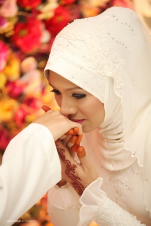 Malaysian bride kisses hand of her new husband