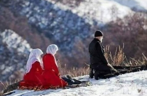 Father leading daughters in prayer, Caucasus Mountains